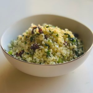 Gorgeous bowl of cauliflower couscous filled with herbs, dried fruit and lemon zest.