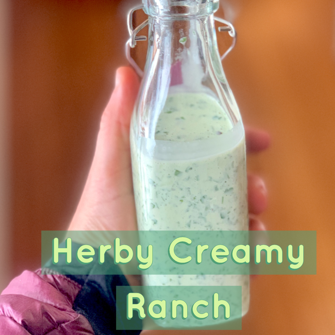 Picure of a hand holding a glass bottle of herby creamy ranch dressing. The bottle is well lit with sunlight and showcasing the beautiful creamy green color of the herbs in the dressing. #healthyrecipes #sproutingvitality #dairyfreedressing #herbrecipes
