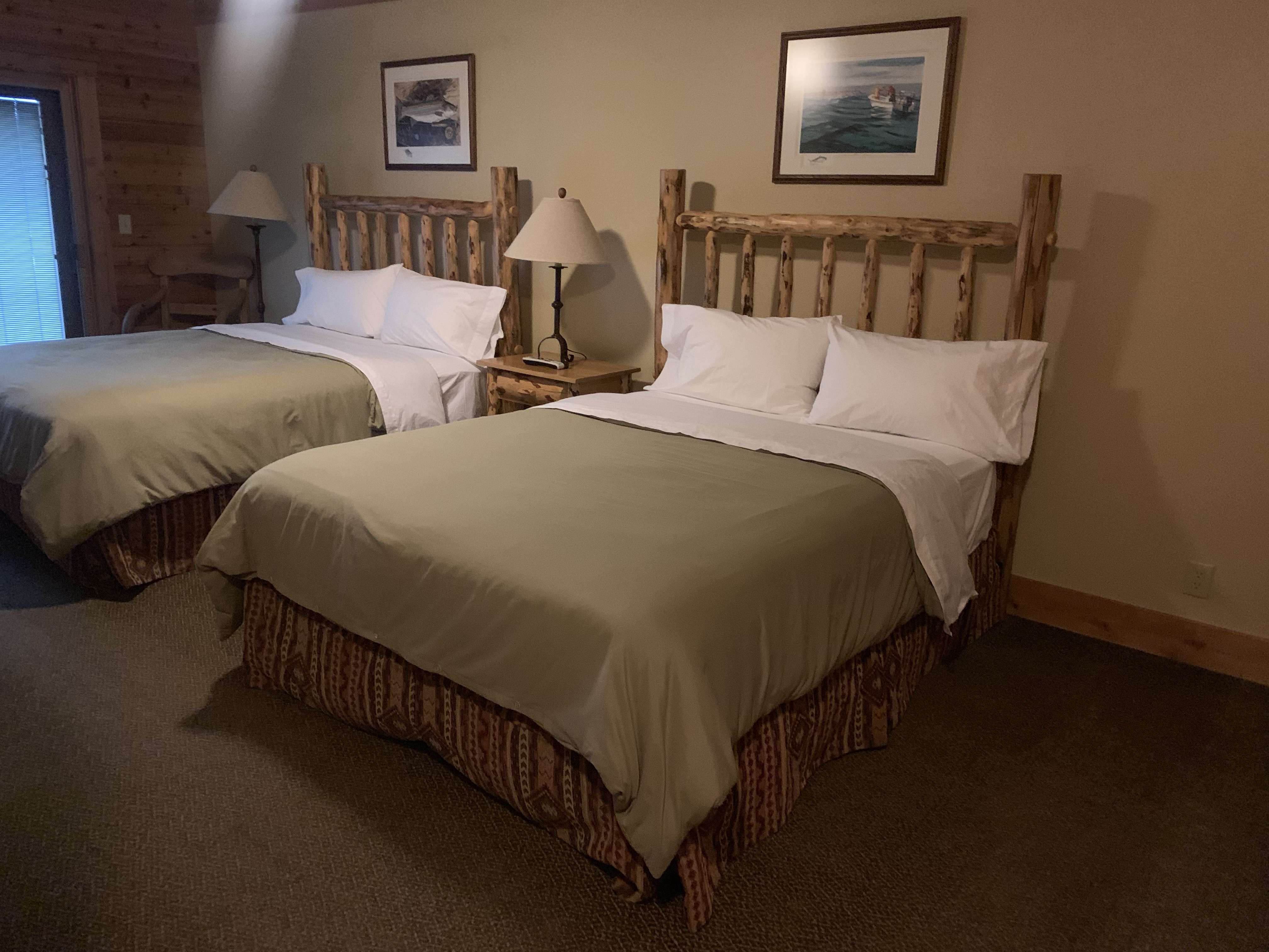 Photo of a room at TroutHunter Lodge, two queen wood framed beds with simple decor and clean room. For more travel and food posts check out www.sprouting-vitality.com #sproutingvitality #kenzinthekitch #mckenzieonthemove