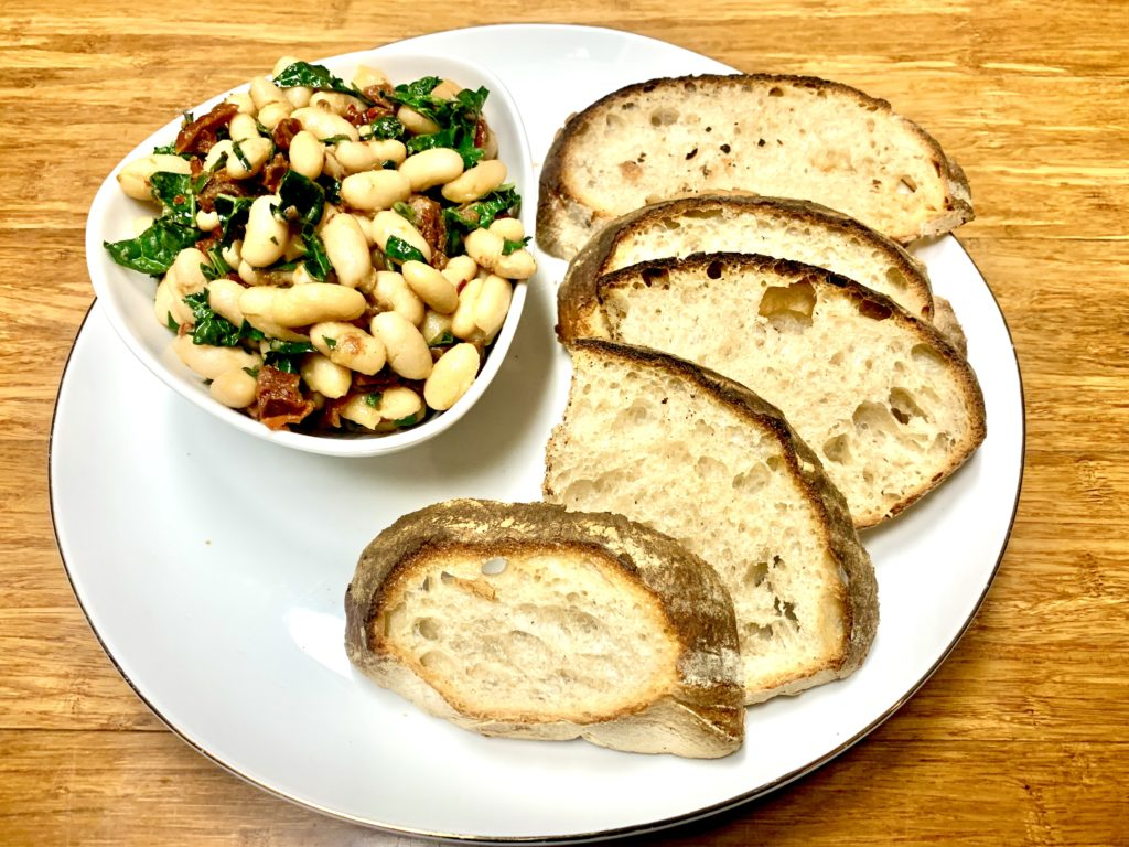 Showcasing a bowl full of seasoned cannellini beans with garlic, sundried tomatoes & kale. Paired with toasted sourdough crostini's to bring this recipe together beautifully. Fore more recipes be sure to follow www.sprouting-vitality.com and on instagram @sproutingvitality. #kenzinthekitch #mckenzieonthemove #sproutingvitality