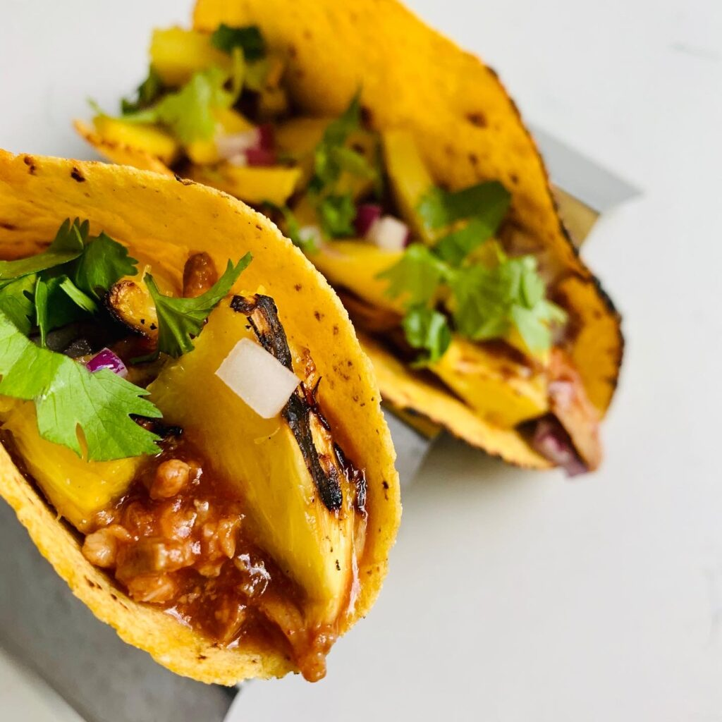 Grilled Pineapple Pulled Pork Tacos that are chocked full of diced red onions, minced cilantro and flavor you can hardly believe in every bite. Grab the recipe. #kenzinthekitch #sproutingvitality #tacos #recipe