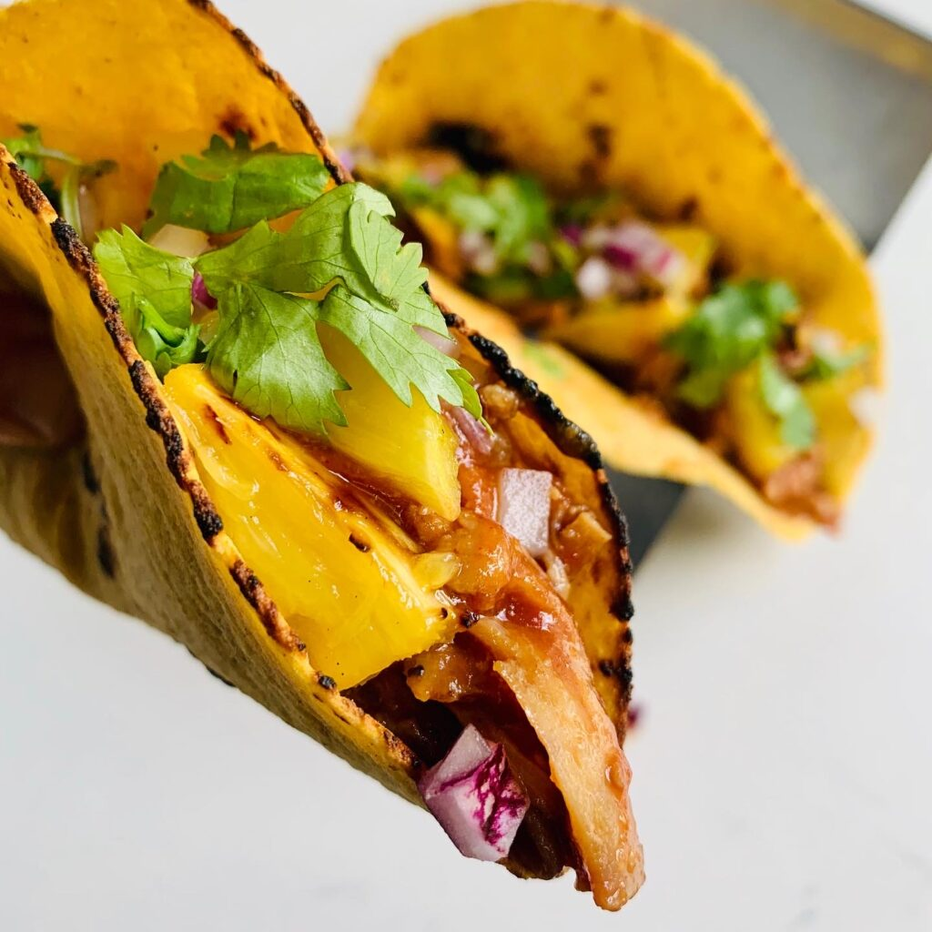 Grilled Pineapple Pulled Pork tacos topped with diced red onion and minced cilantro. Super flavorful taco filled with incredible ingredients. #taco #recipe #kenzinthekitch #sproutingvitality