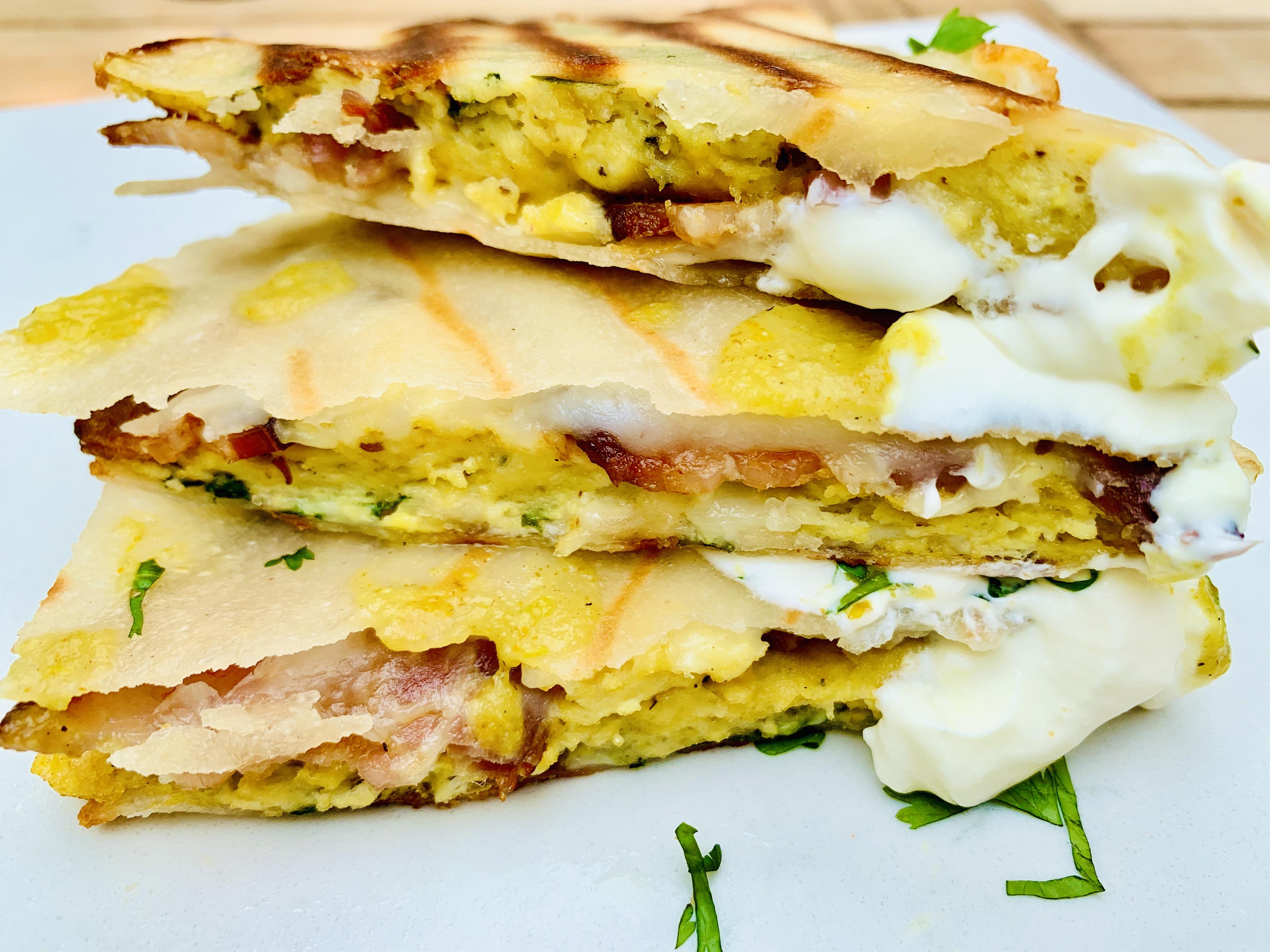 Breakfast Quesadilla stuffed with smoked bacon, green enchilada sauce, sour cream, cilantro and the best siete tortillas. #kenzinthekitch #sproutingvitality #breakfast